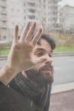 摆在玻璃后的年轻英俊的有胡子的人 库存照片