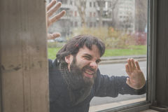 摆在玻璃后的年轻英俊的有胡子的人 免版税库存图片