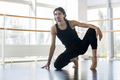 摆在年轻男性的跳芭蕾舞者,人实践的舒展 免版税库存照片