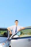 摆在他的在一条开放路的汽车旁边的微笑的人 免版税库存图片