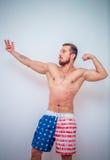 摆在他的肌肉的年轻和适合的男性模型 库存图片