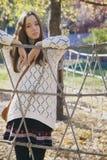 摆在绳索篱芭附近的美丽的年轻十几岁的女孩 库存照片