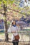 摆在绳索篱芭附近的美丽的年轻十几岁的女孩 免版税图库摄影