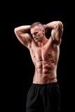 摆在黑背景的英俊的肌肉人 库存照片