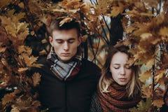 摆在黄色下的时髦的行家夫妇在秋天公园离开 库存图片