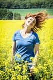 摆在黄色油菜籽领域的愉快的年轻白种人妇女 免版税图库摄影