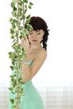 摆在绿色的一套婚礼礼服的美丽的少妇 免版税库存照片