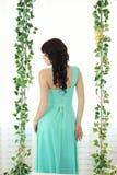 摆在绿色的一套婚礼礼服的美丽的少妇 库存图片
