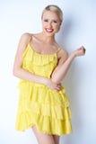 摆在黄色礼服的可爱的白肤金发的少妇 免版税图库摄影
