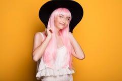 摆在黄色背景的桃红色头发的女孩 图库摄影