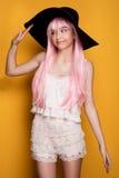 摆在黄色背景的桃红色头发的女孩 免版税图库摄影