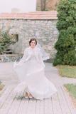 摆在绿色晴朗的公园的美丽的新娘挥动她典雅的婚礼礼服 库存照片
