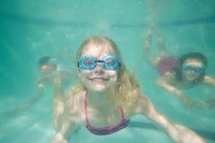 摆在水面下在水池的逗人喜爱的孩子 免版税库存图片