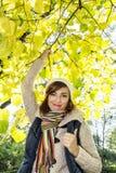 摆在a的山毛榉树下的美丽的年轻白种人妇女 免版税库存照片