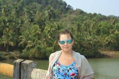 摆在brige的女孩在热带森林附近 免版税库存照片