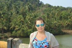 摆在brige的女孩在热带森林附近 库存图片