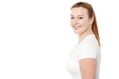 摆在casuals的微笑的妇女 免版税库存照片