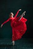 摆在pointe鞋子的芭蕾舞女演员在黑木亭子 免版税库存图片