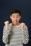 摇两个拳头的生气的年轻亚裔人 免版税图库摄影