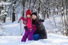 摇他们的手的母亲和女儿在冬天森林里 免版税图库摄影