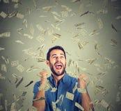摇动拳头的愉快的人庆祝成功尖叫在金钱雨下 免版税库存照片
