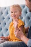 摇她的手的愉快的好女孩 免版税库存照片