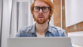 摇对没有的头,红头发人研究膝上型计算机的胡子人 股票视频