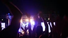 摇手在音乐会党,激动的在音乐节的观众晃动的手,胳膊的爱好者上升了人 影视素材