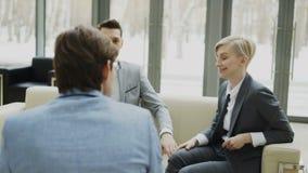 摇摄射击了与坐男性的商务伙伴的快乐的女实业家谈的和duscussing的未来协议  股票视频