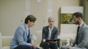 摇摄射击了有duscussing与男性企业同事的数字式片剂的女实业家坐在现代的长沙发 股票录像