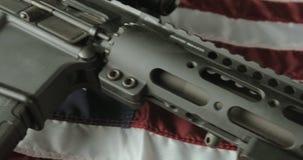 摇摄说谎在一面美国国旗的被射击攻击步枪 股票录像