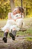 摇摆与被充塞的玩具熊的女孩 免版税库存照片