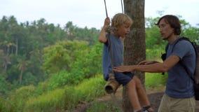 摇摆他的年轻人的慢动作射击一点儿子摇摆在一个热带公园 童年概念 股票视频