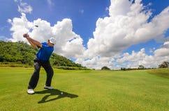 摇摆他的齿轮和命中的高尔夫球运动员 免版税库存照片
