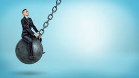 摇摆在一个大击毁的球和查寻在蓝色背景的商人 免版税库存照片