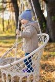 摇摆在一把垂悬的椅子的愉快的孩子在一个森林里在秋天 免版税库存照片