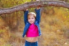 摇摆在一根树干的儿童女孩在杉木森林里 库存图片