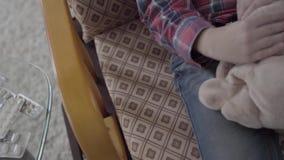 摇摆在他的椅子的未被认出的小男孩,在他的手上拿着一个软的玩具紧密  影视素材