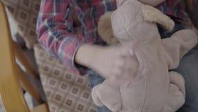 摇摆在他的椅子的未被认出的小男孩,在他的手上拿着一个软的玩具紧密  股票视频