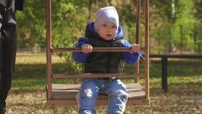 摇摆在儿童操场的男婴在公园 有愉快的孩子美好时光户外 影视素材