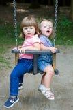 摇摆在公园的愉快的小女孩 免版税库存照片