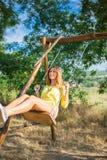 摇摆在公园的美丽的少妇 免版税库存照片