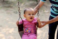 摇摆在公园的逗人喜爱的男婴 图库摄影