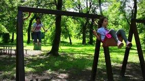 摇摆在公园,慢动作的愉快的女孩 股票视频