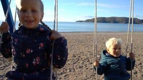摇摆在摇摆的一个三岁的男孩和一个六岁的女孩在海岸的一个晴朗的早晨 影视素材