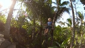 摇摆在摇摆的一个小男孩的UHD慢动作射击在热带密林 童年概念 两年飞机婴孩推车儿童女孩老休眠小的特殊的旅行 影视素材