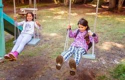 摇摆在摇摆的两个愉快的小女孩在儿童的游乐场 库存图片