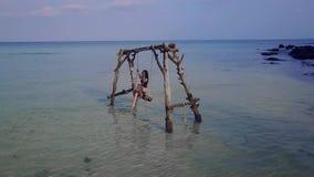 摇摆在摇摆的女孩在海 水摇摆 失去的天堂无人居住的海岛 股票录像