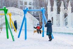 摇摆在摇摆的小女孩在镇中心在冬天 免版税库存图片
