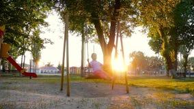 摇摆在摇摆的微笑的小女孩在金黄夏天日落 乐趣在公园,在森林,本质上 一个温暖的夏日 股票视频